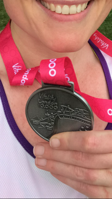 Me holding a medal from London's Vitality 10k race.  theunravelling.net